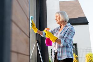 ältere Dame putzt Fenster